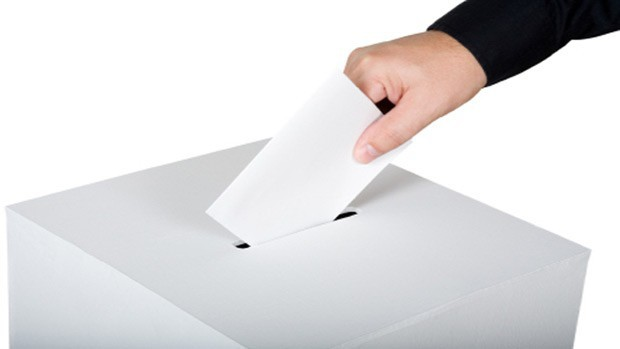 A hand with ballot and ballot box